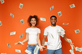 Financial success. Excited young african-american couple standing under money banknotes shower, orange background