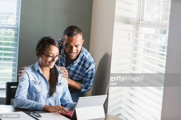 Young black couple, woman on computer paying bills