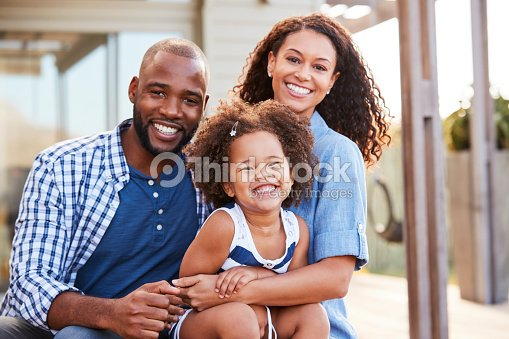 Young black family embracing outdoors and smiling at camera : Stock Photo