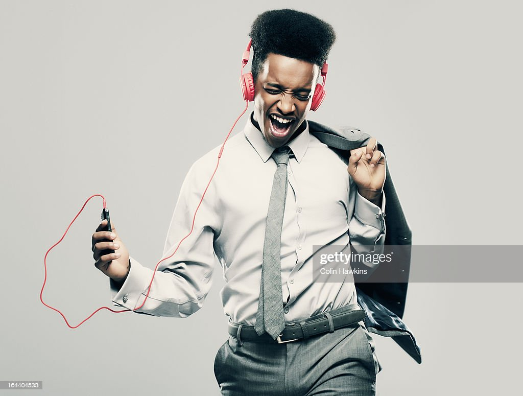 Young Black Male businessman listening to music : Stock Photo