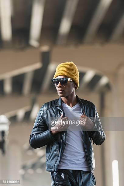 Jóvenes negro man, decorado en una gorra con sombrero y cuero