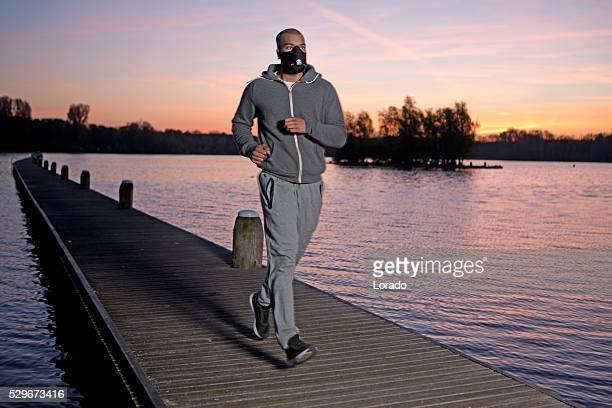 Young black man exercising at dawn at lake