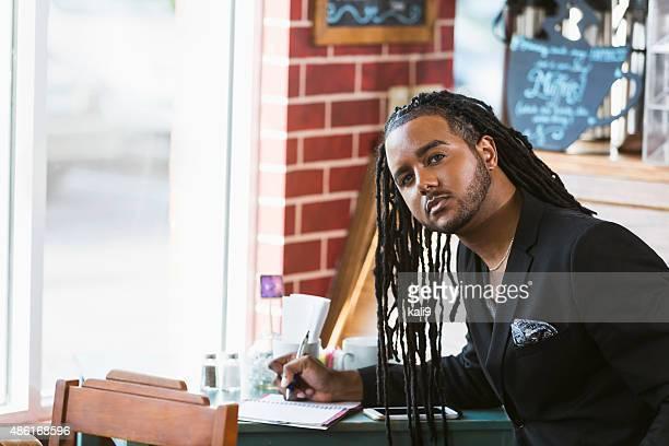 Jeune homme dans le café noir en écrivant en ordinateur portable