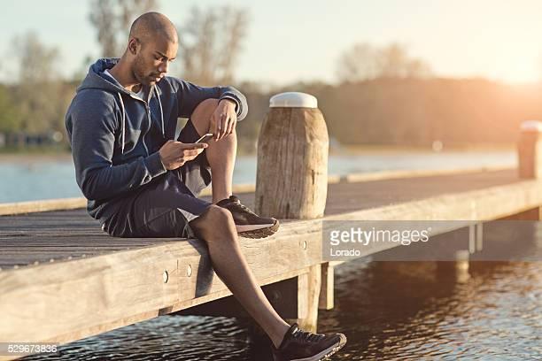 Young black man using smartphone at dawn at lake