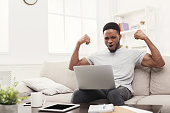 Young black man with raised arms working on laptop and celebrating success, sitting on the couch at home, copy space