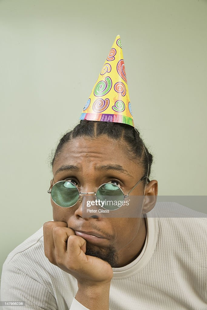 Young black man with party hat and sunglasses. : Stock Photo