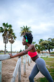 Young black runner listening music at training