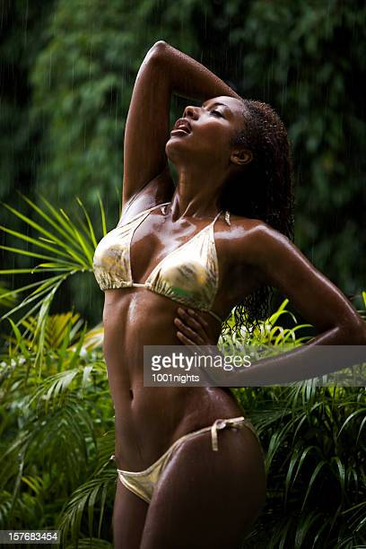 Young black woman dancing under the rain