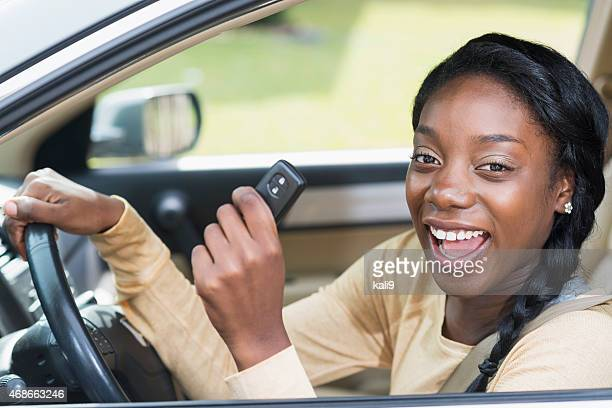 Young black woman driving car