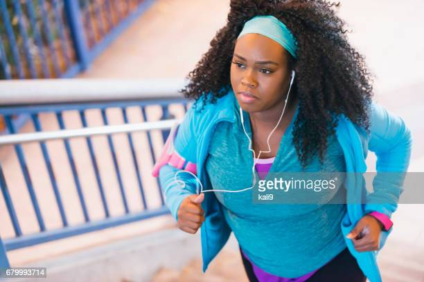 Young black woman exercising, running up steps