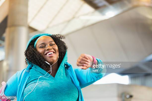 Young black woman exercising, using fitness tracker