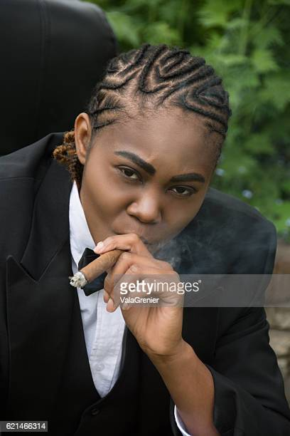 Young black woman in male drag,leaning forward with cigar.