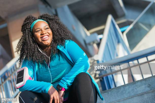Young black woman in sports clothing with headphones