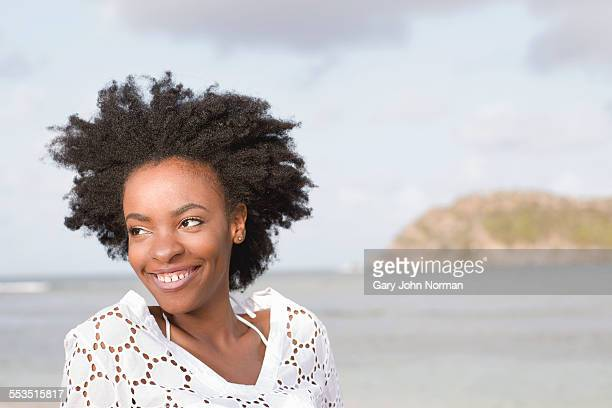 Young black woman on the beach smiling.
