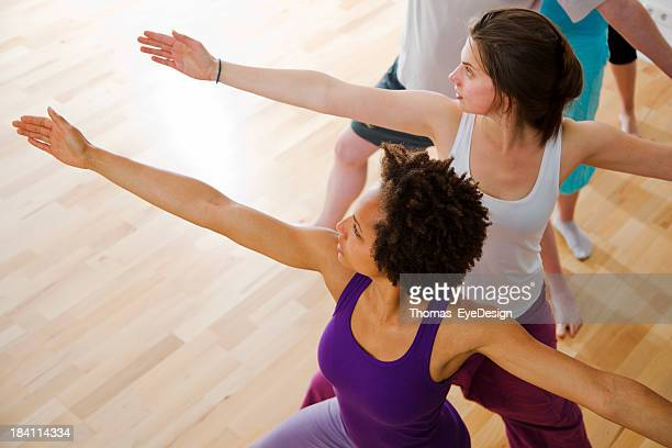 Young black yoga instructor at classroom showing exercise