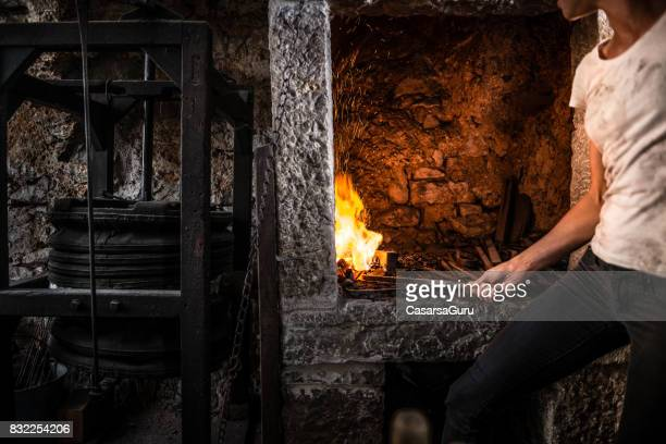 Young Blacksmith Woman Preparing a Fire in Blacksmith Shop