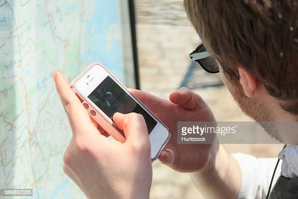 Young blind man at a bus stop using assistive technology to help with map
