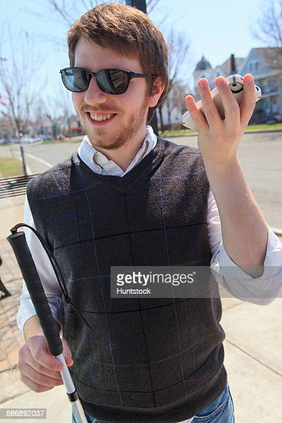 Young blind man with cane using assistive technology in his neighborhood