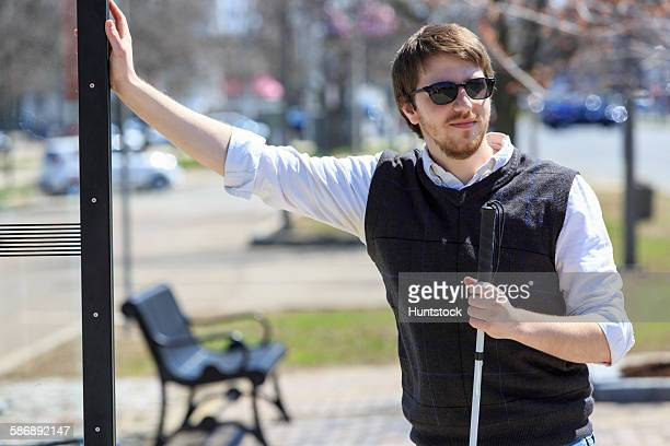 Young blind man with cane waiting at a bus stop