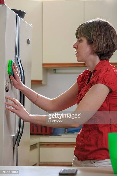 Young blind woman cleaning her refrigerator in her kitchen