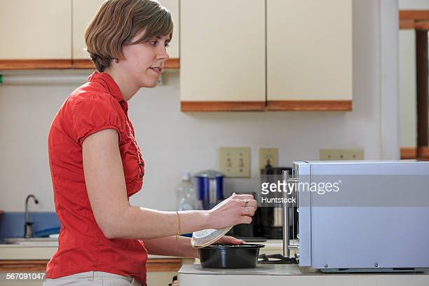 Young blind woman cooking in her kitchen with her microwave