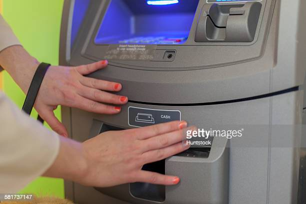 Young blind woman using a bank ATM