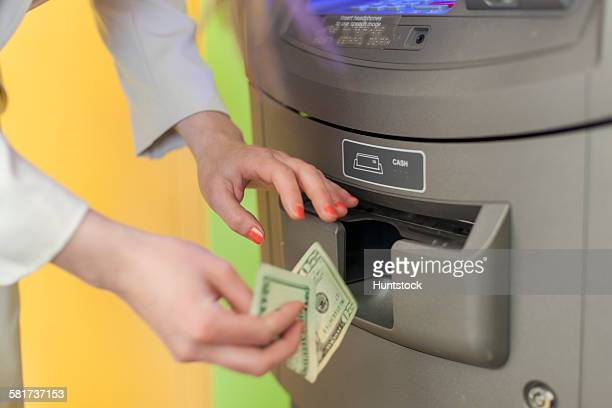 Young blind woman using a bank ATM to get money