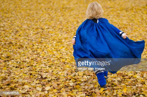 young blond boy running, super hero cape flying : Stock Photo