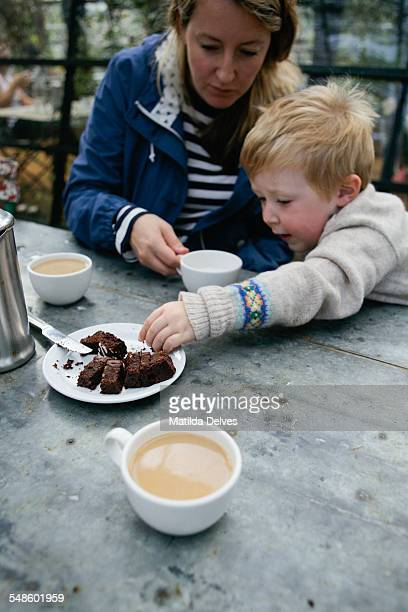Young blond boy with his mother eating cake