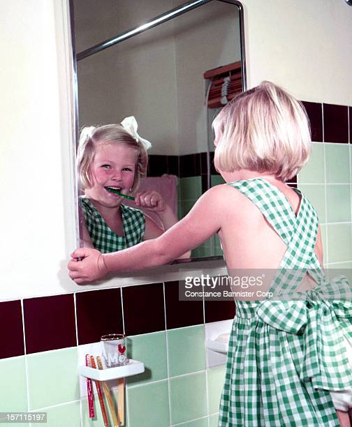 A young blond girl brushing her teeth 1943