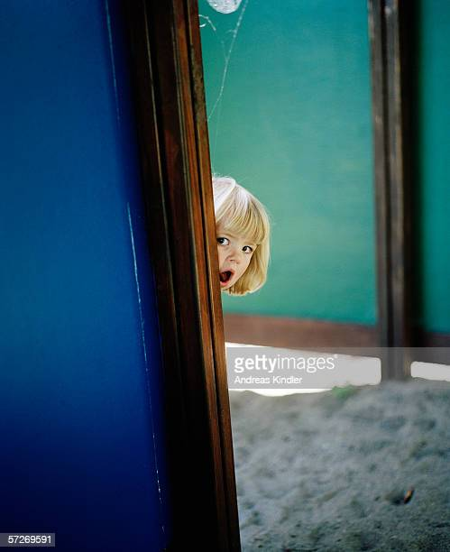 A young blond girl peeking from behind a plank.