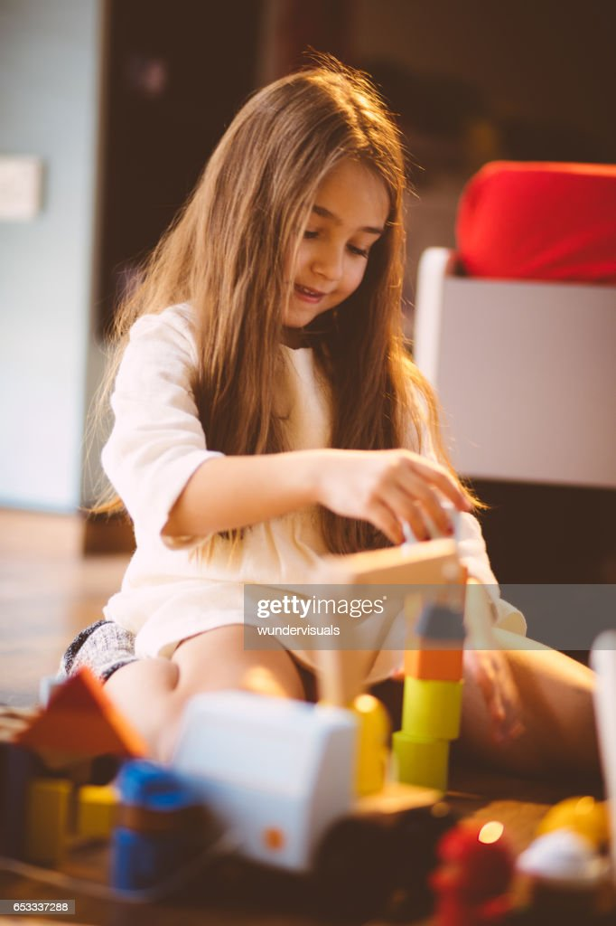 Young blond girl playing with toy blocks on the floor : Stock-Foto
