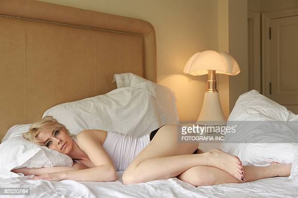 Young blond lady lying in her bed. Looking at camera.