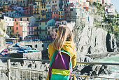 Young blond tourist woman in bright clothes with backpack standing near fence and looking at traditional colorful houses and Ligurian sea, Riomaggiore, Cinque Terre, Italy