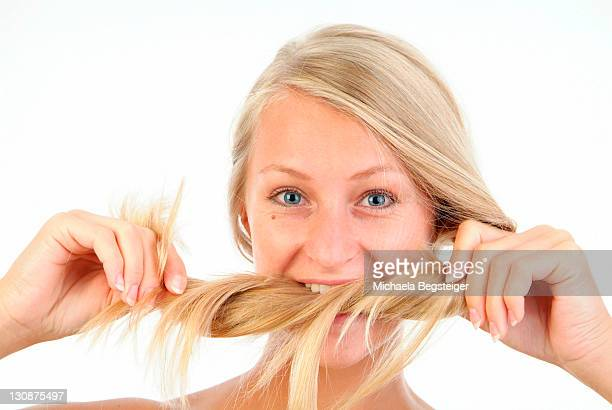 young, blond woman biting in her hair