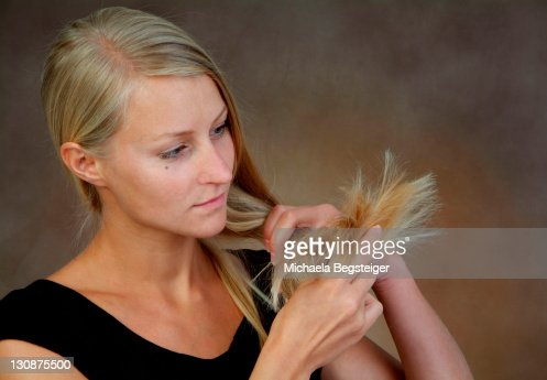 young, blond woman controls hair tips