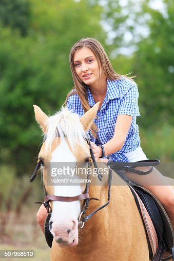 Young blond woman on the horse