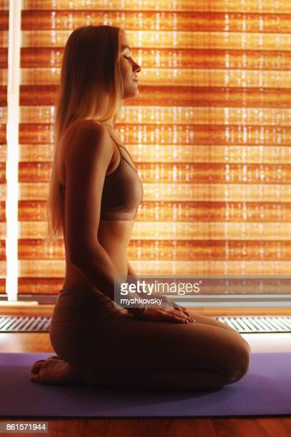 Young blond woman practicing yoga at yoga studio