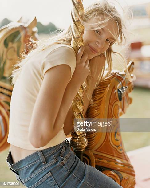 Young Blond Woman Sitting on a Carousel Horse, at a Fairground