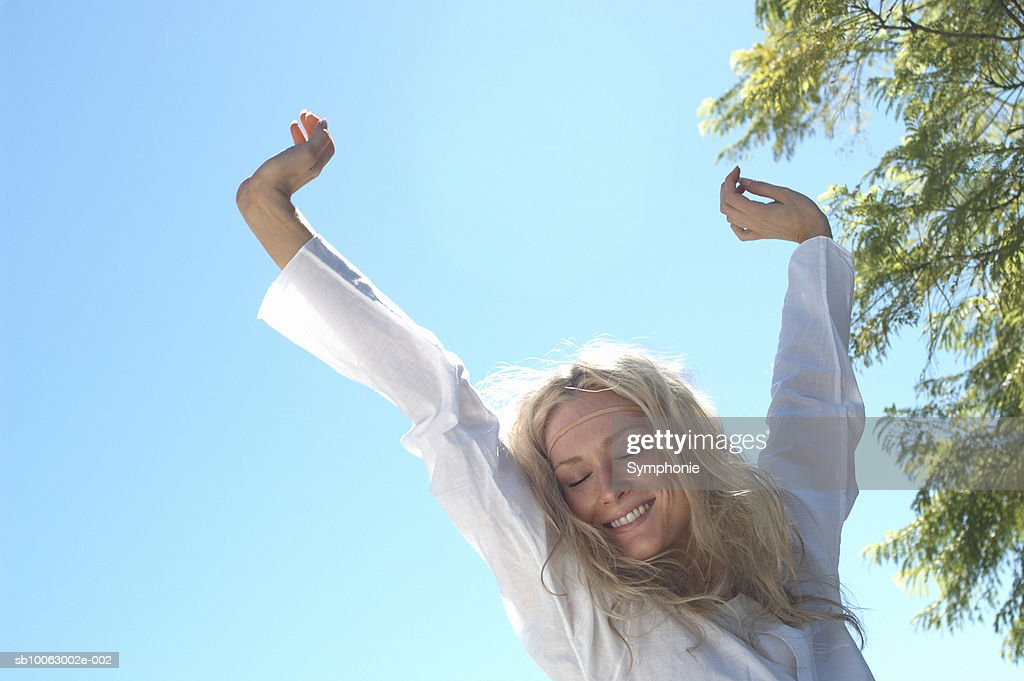 Young blond woman smiling stretching arms above head : Stock Photo