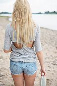 Young blond woman standing on the beach, back view