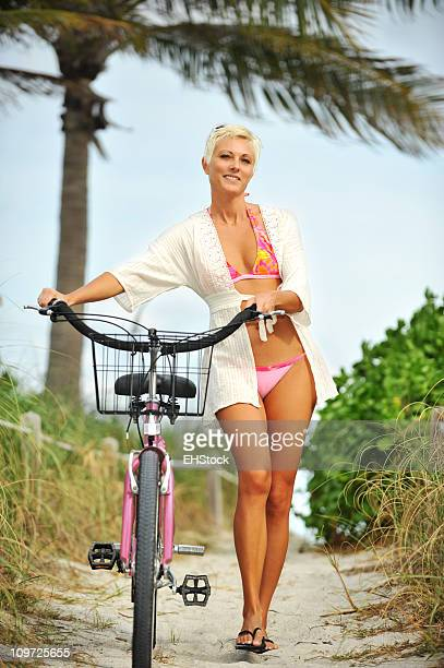 Young Blond Woman walking Bicycle at beach wearing coverup