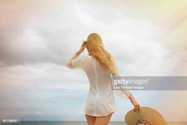 Young blond woman with sunhat looking out to sea from Miami Beach, Florida, USA