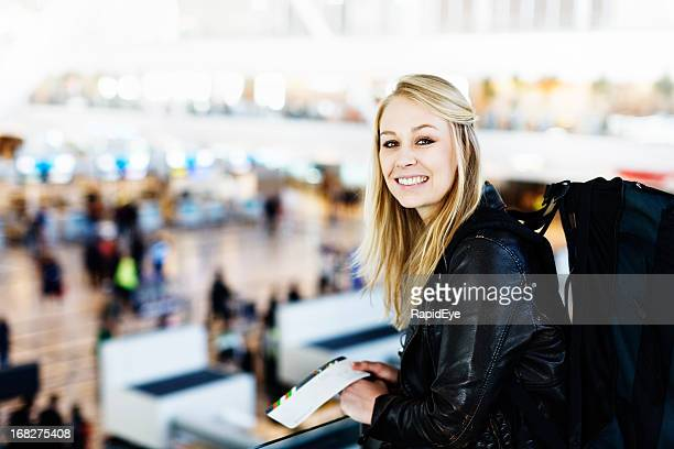 Young blonde backpacker with boarding pass looking over airport check-in