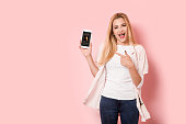 Young blonde girl is enthusiastic and points at her smartphone