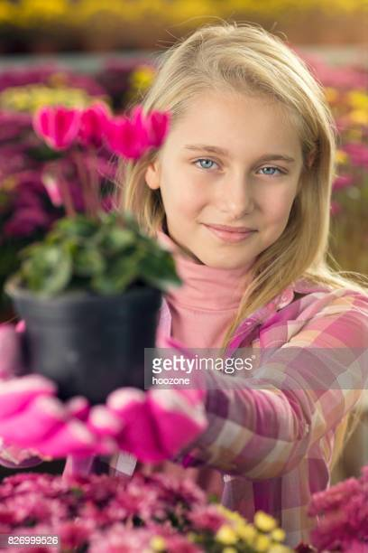 Young blonde girl planting flowers