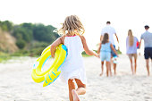 Young blonde girl running on the beech. Summer vacation and travel concept