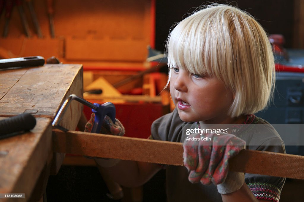 Young blonde girl sawing and doing carpentry : Stock Photo