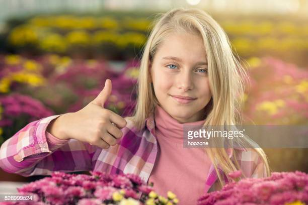Young blonde girl showing thumbs up in greenhouse