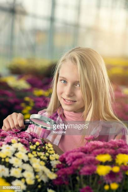 Young blonde girl using magnifying glass at greenhouse